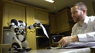 videoblocks-robot-helping-man-at-home-kitchen-table-desk-doing-office-work-walks-and-hands-man-pen-artificial-intelligence-and-future-robotics-technology-with-humanoid-cyborg-futuristic-