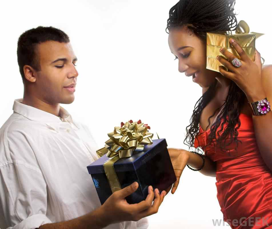 man-in-white-shirt-giving-gift-to-woman-in-red-dress