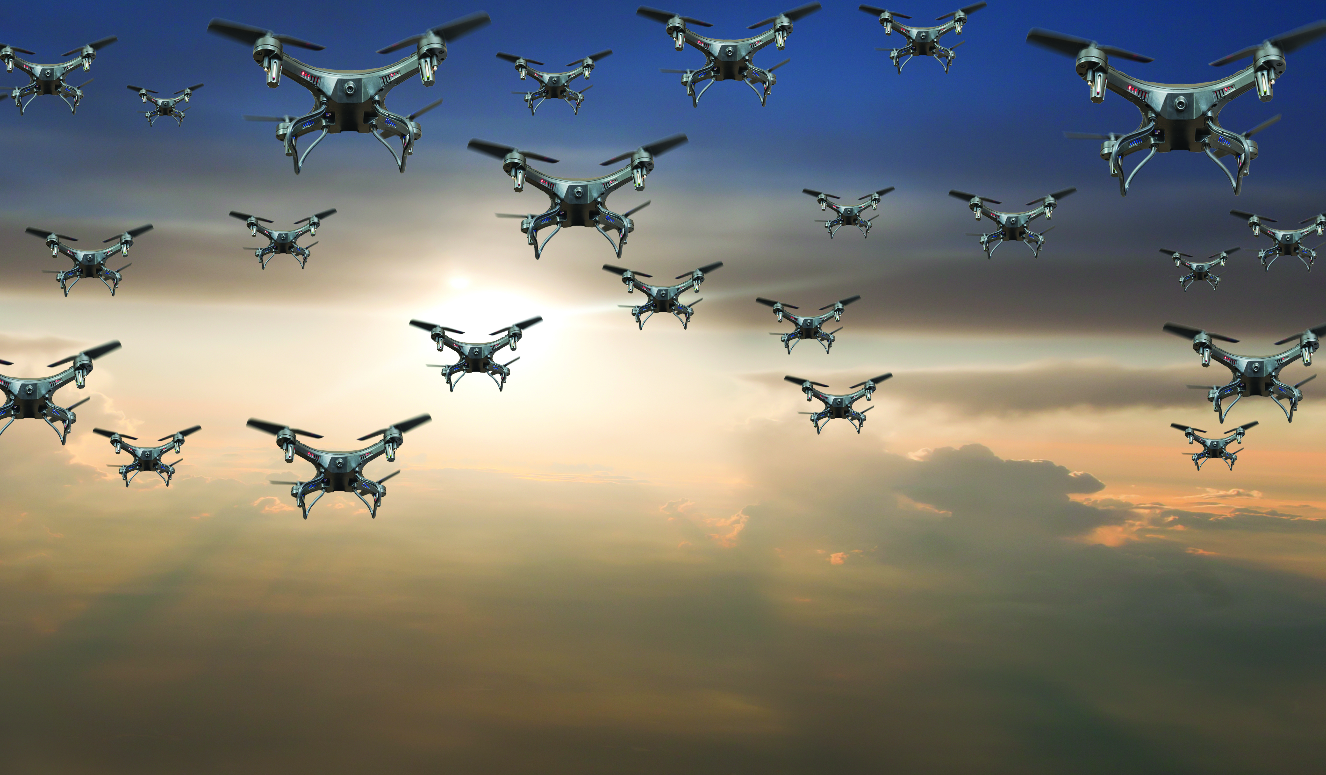 Flock of drones in the sky at sunset